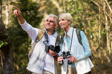 middle age couple: active middle aged couple hiking outdoors in forest