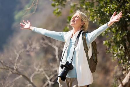 senior female photographer arms open on top of the mountain Stockfoto