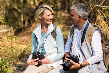 couple relaxing: cheerful middle aged couple resting in mountain valley Stock Photo