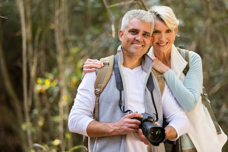 middle age: portrait of lovely couple hiking in forest