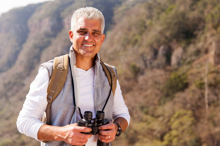 happy mid age man on top of the mountain with binoculars Stock Photo