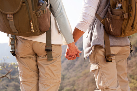 couple nature: back view of couple holding hands hiking in mountain