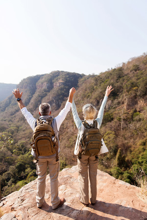 mid age hikers arms open on mountain cliff