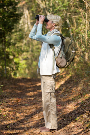 mid age: side view of mid age woman using binoculars bird watching in forest