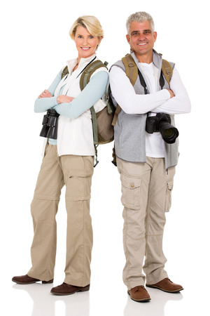 arms crossed: cute middle aged couple tourists posing isolated on white Stock Photo