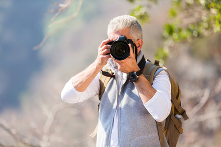 senior men: middle aged man taking photos in mountain valley with dslr camera Stock Photo