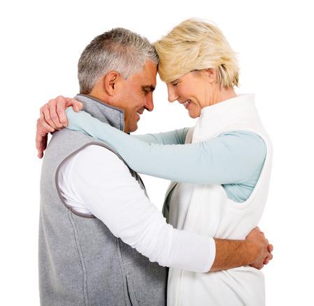 senior adult man: lovely senior couple hugging with eyes closed on white background