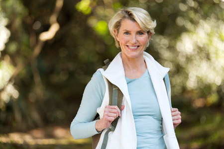 smiling middle aged female hiker in mountain valley