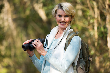 middle age: portrait of beautiful female hiker with binoculars Stock Photo
