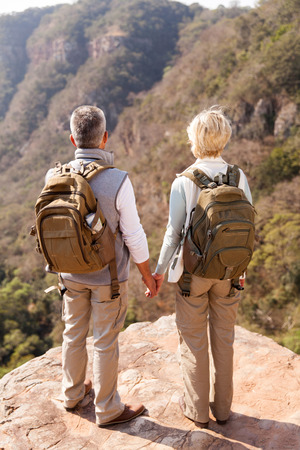 cliff edges: senior hikers with backpacks enjoying the view from top of a mountain