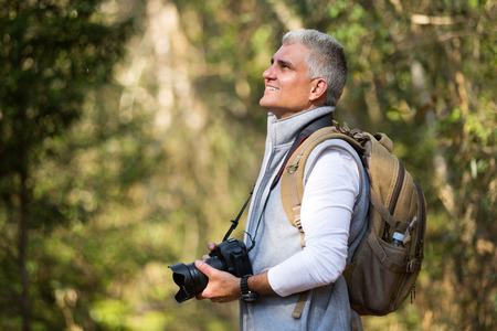 dslr camera: handsome man hiking in mountain with dslr camera