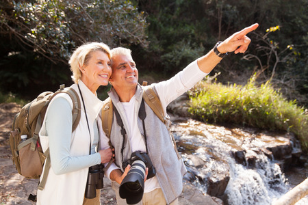 tourists: cheerful senior couple hikers pointing in mountain valley