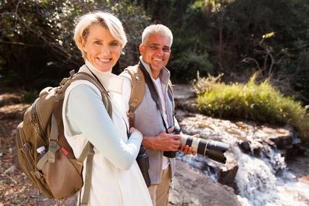 caminhantes de meia idade alegres que relaxam pelo rio desfrutando de atividade ao ar livre