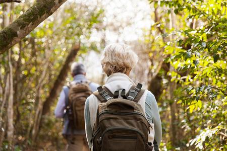 Pohled zpět na pár pěší turisti společně v lese
