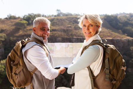 middle aged couple: happy middle aged couple with map looking back