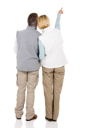 back view: back view of senior couple pointing empty space isolated on white