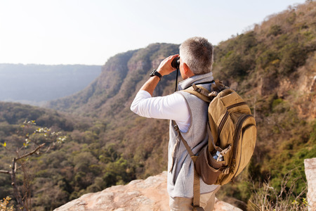 middle aged male hiker using binoculars on top of the mountain