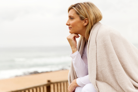 one person: thoughtful woman with hand on chin looking away Stock Photo