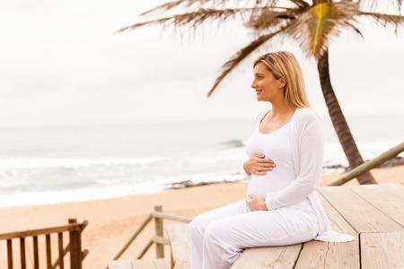 ragazze bionde: Donna incinta felice sulla spiaggia