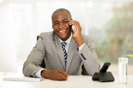 african business man: cheerful young african business man talking on mobile phone Stock Photo