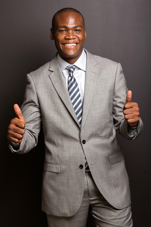 standing up: happy young african american man giving thumbs up on white background Stock Photo