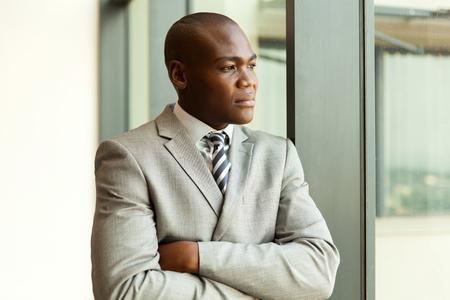 persona pensando: Hombre de negocios africano joven reflexivo con los brazos cruzados Foto de archivo
