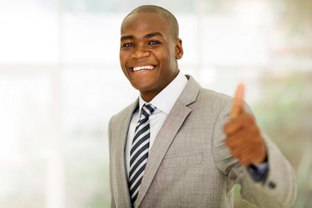 afroamericana: alegre africano ejecutivo de negocios americano que da el pulgar para arriba en la oficina
