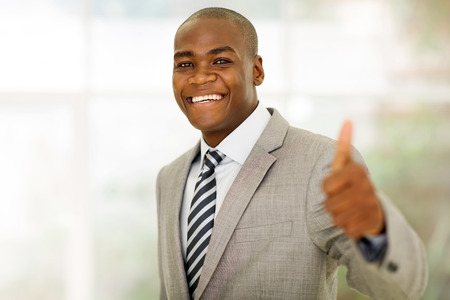 african: cheerful african american business executive giving thumb up in office