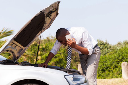 young man with broken down car with bonnet open calling for help