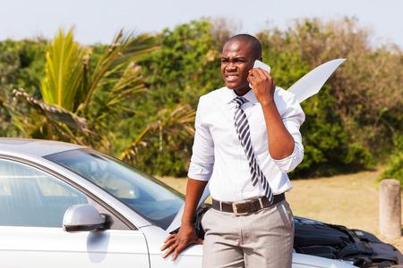 broken down: worried african american man with broken car calling for help