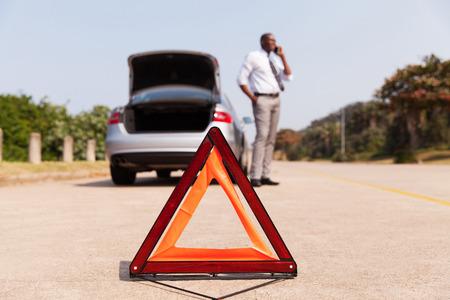 chofer: conductor masculino africano pidiendo ayuda despu�s del coche se rompi� hacia abajo por el lado de la carretera