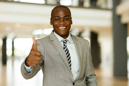 look up: confident afro american business man thumb up Stock Photo