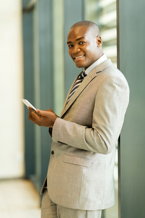 african business man: handsome young african business man holding cell phone Stock Photo
