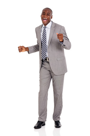 excited young african businessman dancing over white background
