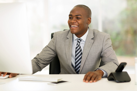 sitting at desk: happy young african businessman working on computer