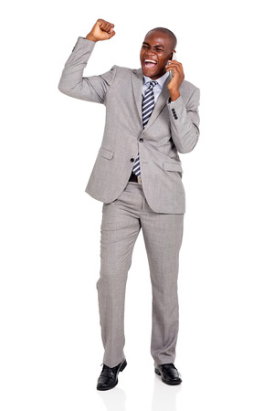 african business man: excited young african business man talking on cell phone