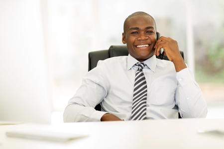 relaxed business man: african business man talking on landline phone in modern office Stock Photo