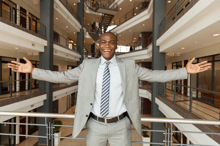open business: excited african businessman with arms outstretched in modern office building