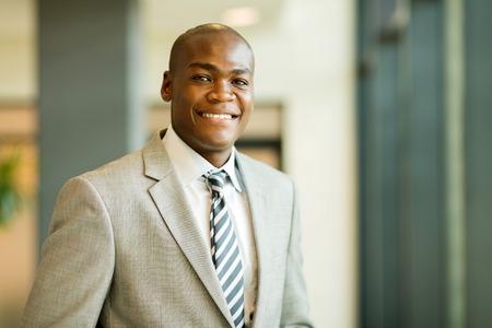 relajado: retrato de cerca de joven empresario afroamericano en el cargo