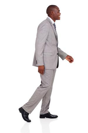 persona caminando: vista lateral del afroamericano joven empresario caminando