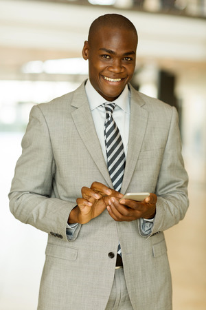 white suit: portrait of smiling businessman using smart phone in office