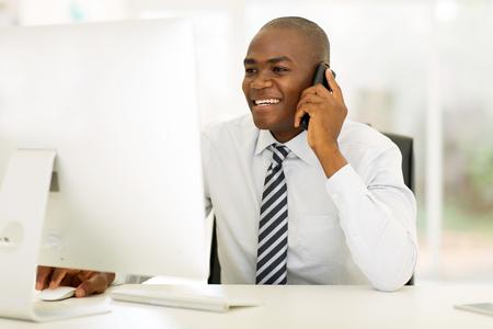 sonriente: llamada de teléfono de fabricación de negocios sonriente afroamericano