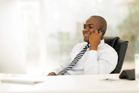 ejecutivo en oficina: feliz ejecutivo de negocios hablando por teléfono fijo africano