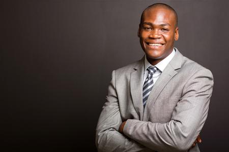 erfolgreichen afrikanischen Geschäftsmann mit den Armen auf schwarzem Hintergrund gefaltet