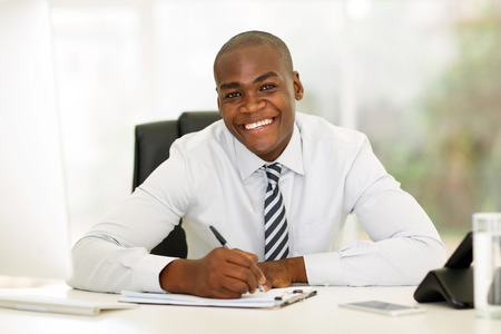 african business man: happy african corporate worker working in office Stock Photo