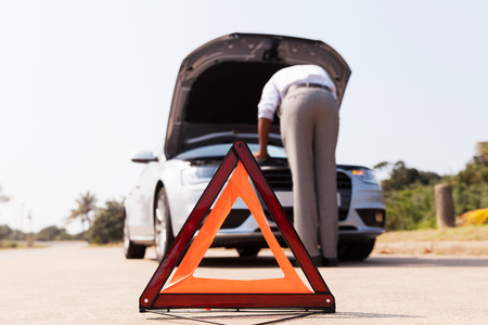 warning triangle: driver trying to figure out how to fix broken down car with red triangle to warn other road users