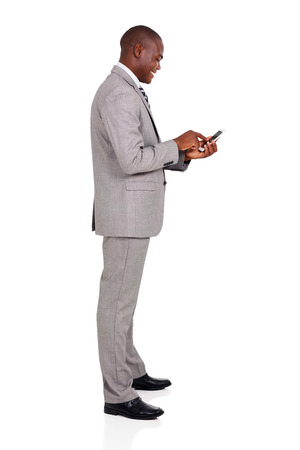 working man: side view of afro american businessman using smart phone
