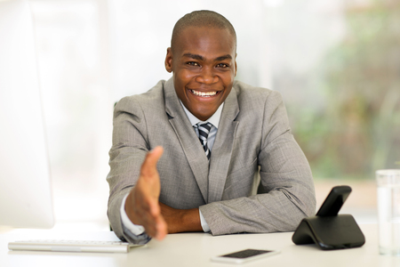 saludo de manos: amigable empresario africano ofreciendo apretón de manos en la oficina Foto de archivo