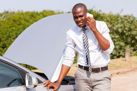 young african man calling for assistance with his car broken down by the roadside Stockfoto