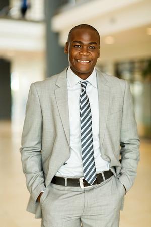 hombres negros: sonriente hombre de negocios negro posando en la oficina